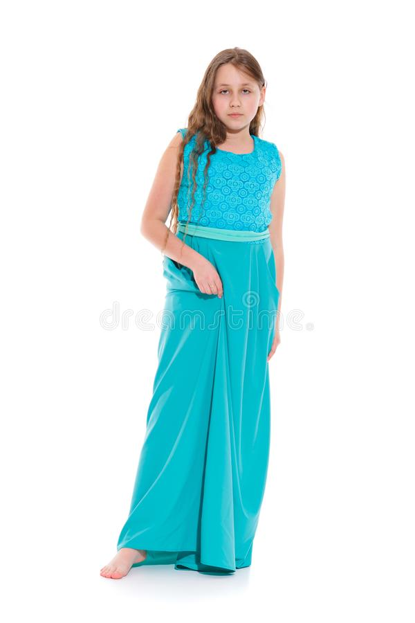 Girl 10-11 years old in a long emerald dress with bare feet. royalty free stock photos