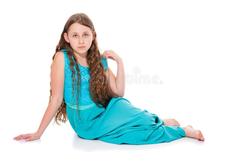 A girl of 10-11 years old in a long emerald dress with bare feet sitting on the floor. Isolation on a white. stock photo