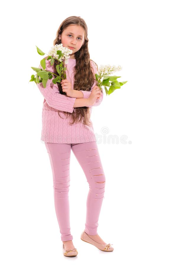 Girl 10-11 years old in a pink suit holding white lilac in her hands. Isolation on a white. stock image