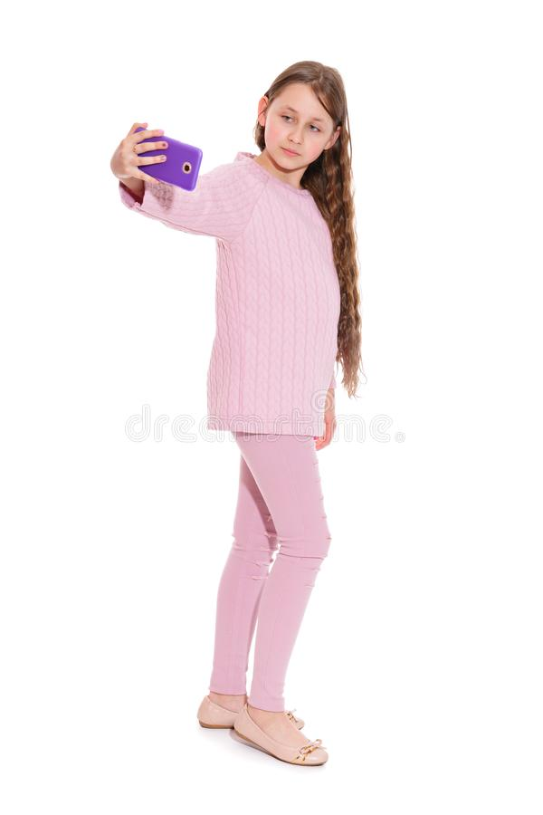 A girl of 10-11 years old in a pink suit takes a selfie from a smartphone. Isolation on a white. stock image