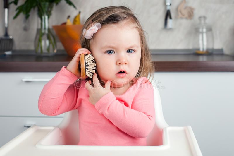 Girl 2 years old playing with a comb at home - portraying an emotional conversation on the phone. stock images