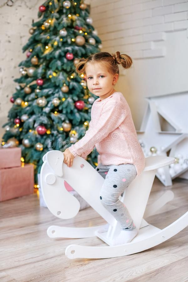 Girl 3 years old riding a horse. Concept New Year, Merry Christm stock photo