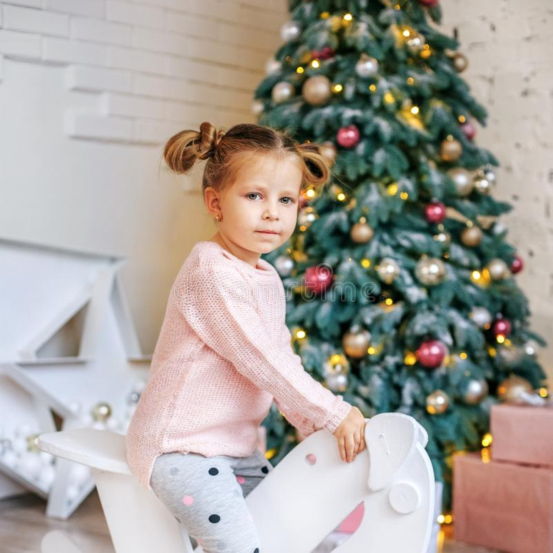Girl 3 years old riding a horse. Concept New Year, Merry Christm. As, holiday, vacation, winter, childhood royalty free stock photography