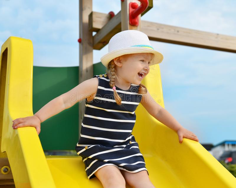 Girl of 3 years old sliding outdoor royalty free stock photography
