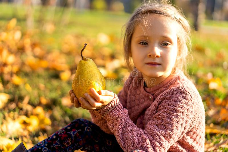 Girl 4 years old walks in autumn park holding a pear royalty free stock images