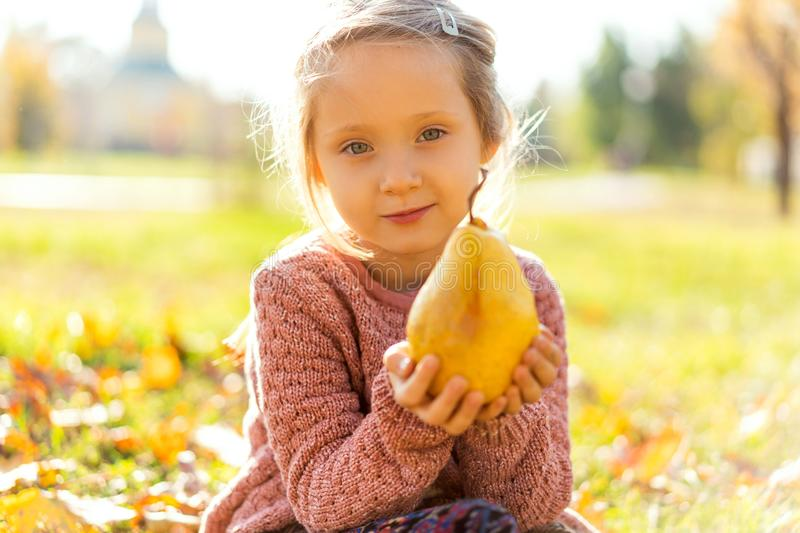 Girl 4 years old walks in autumn park holding a pear royalty free stock image