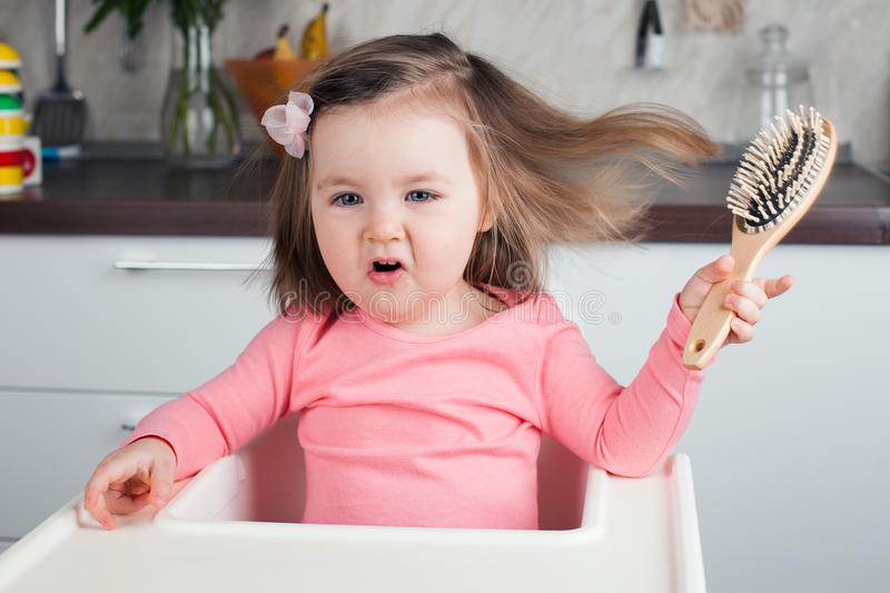 Girl 2 years playing with a comb at home - learning to comb her long hair, writhes doing funny and serious faces. stock photos