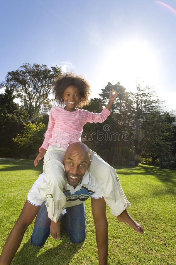 Girl (6-8 years) sitting on father outdoors, smiling, portrait royalty free stock photography