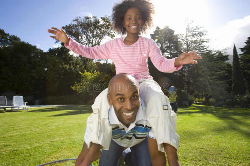 Girl (6-8 years) sitting on father outdoors, smiling, portrait royalty free stock image