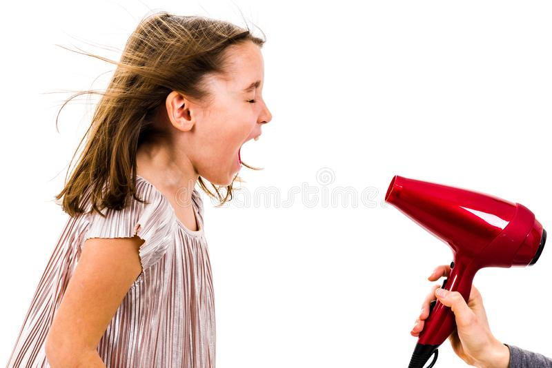 Girl is yelling, shouting at blow dryer - hair dryer royalty free stock image