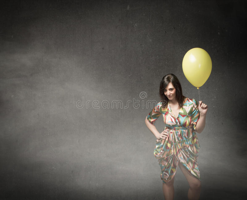 Girl with yellow balloon on hand. People emotions and expressions in dark background stock photos