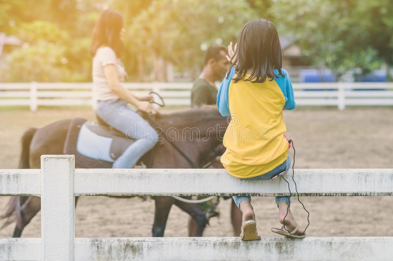 Girl in yellow and blue shirt use smartphone to take photos at the horse riding field royalty free stock photo