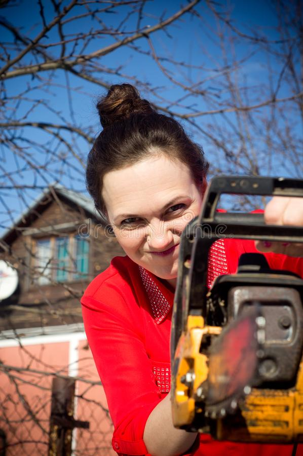 Girl with a chainsaw royalty free stock image