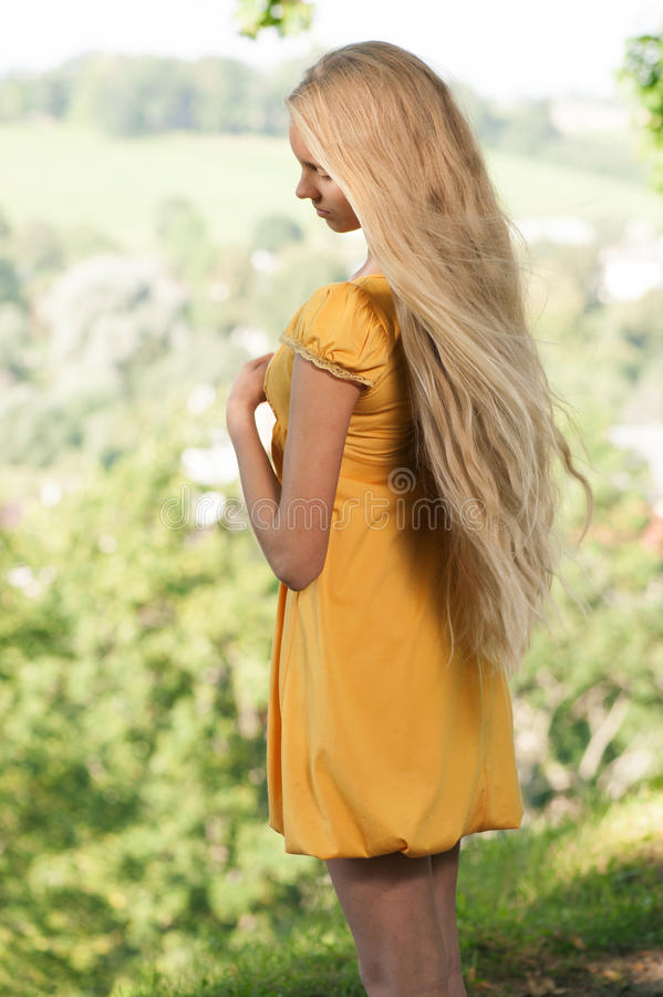 Girl in yellow dress against rural landscape background stock photos