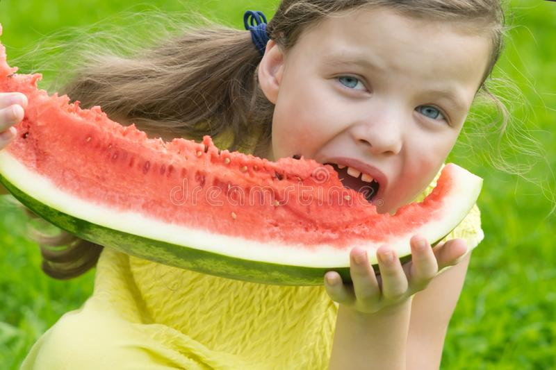 Girl in a yellow dress eats a slice of red watermelon royalty free stock photo