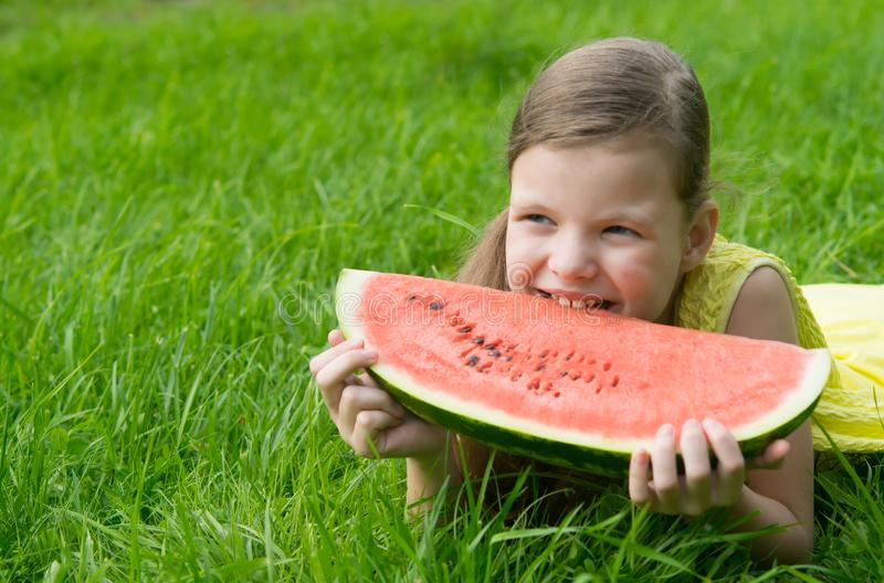 A girl in a yellow dress lying on a green lawn, eating a large slice of watermelon. against the green lawn. there are places for stock photo