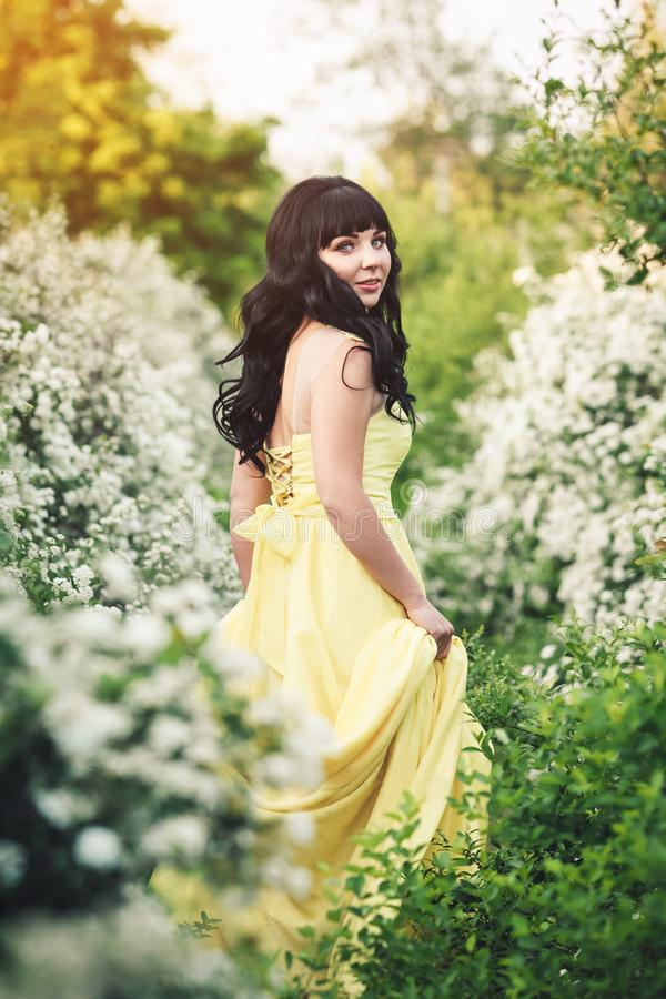 Girl in yellow dress is standing between flowering spiraea and sunbeam shines on her. royalty free stock images