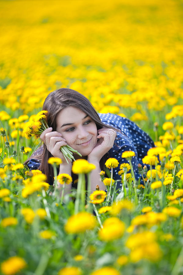 Girl in yellow flowers. She is enjoying free time laying on a field stock images