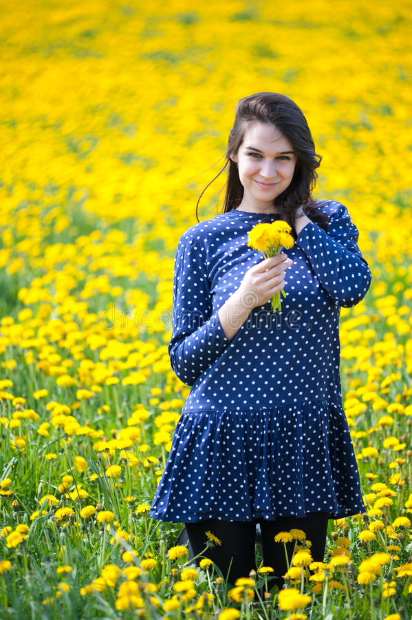 Girl in yellow flowers. She is enjoying free time laying on a field royalty free stock photography