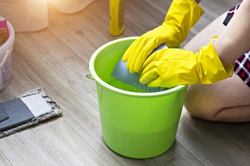 A girl in yellow gloves wets a rag in a bucket, cleaning equipment domestic stock photo