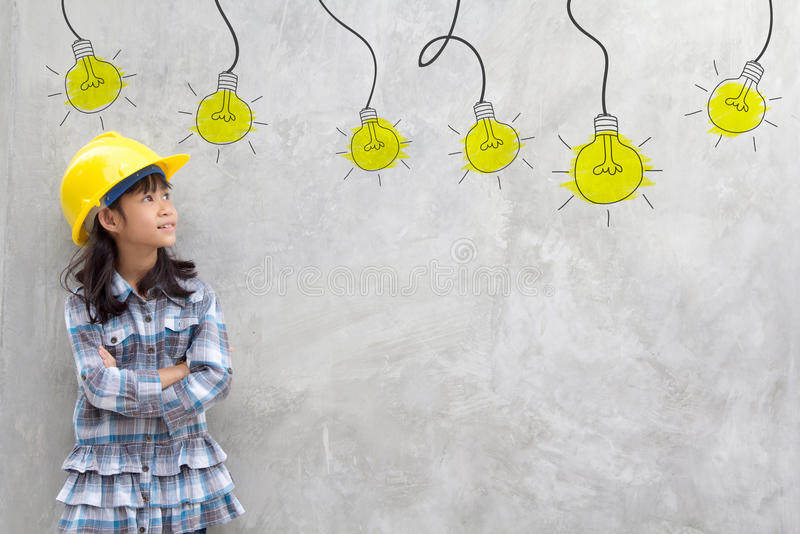 Girl in yellow helmet with light bulb ideas royalty free stock photos