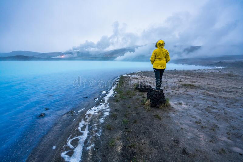 Girl with yellow hiking jacket stands on volcanic rock looking towards Geothermal powerplant at the blue lagoon in Jarabodin/Myvat stock photography