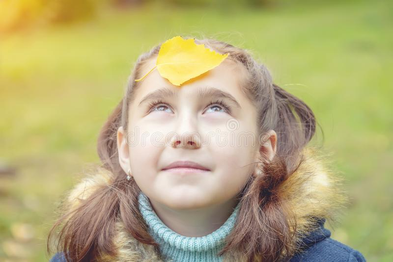 Girl with yellow leaves on her face. Smiles royalty free stock photos
