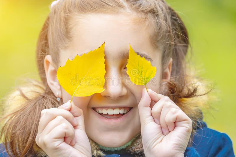Girl with yellow leaves on her face. Smiles stock photography