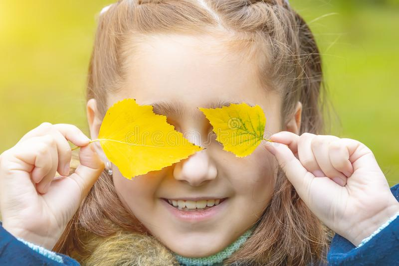 Girl with yellow leaves on her face. Smiles royalty free stock photo