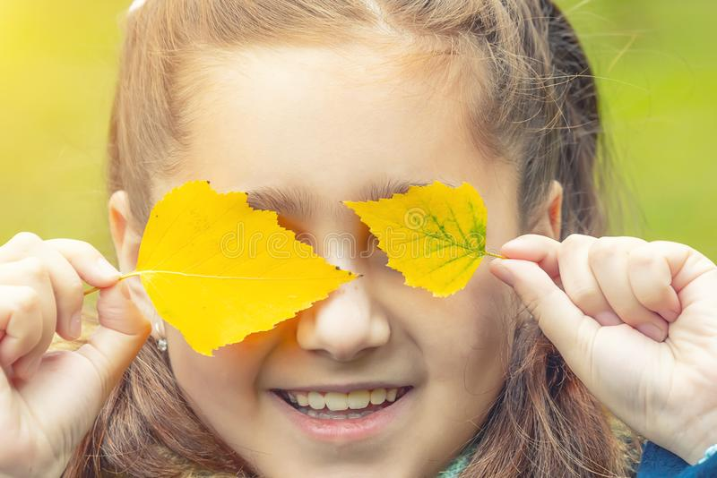 Girl with yellow leaves on her face. Smiles royalty free stock image