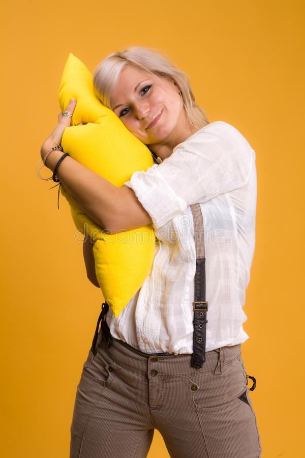 Girl with a yellow pillow stock image