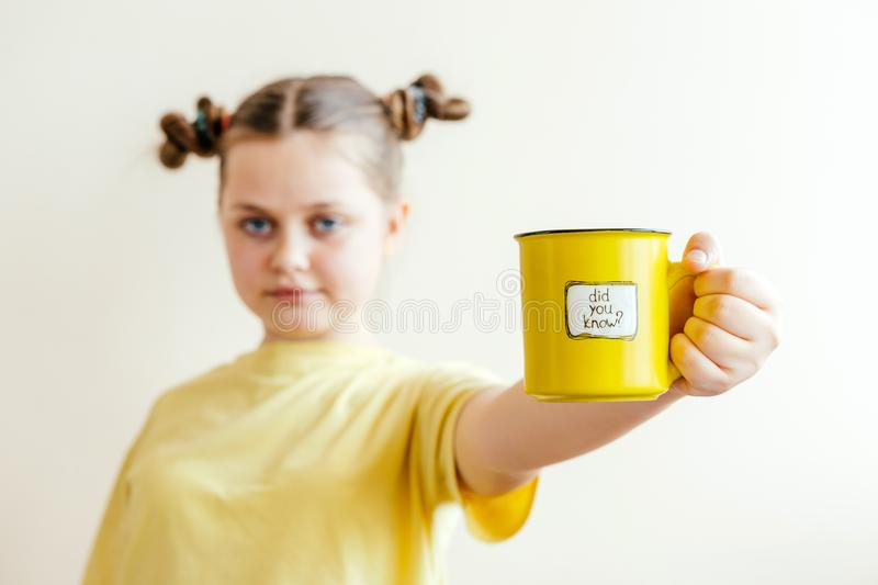 A girl with a yellow ring in her hand, on which was written Did you know. A girl in a yellow T-shirt with a yellow ring in her hand, on which was written Did you royalty free stock images