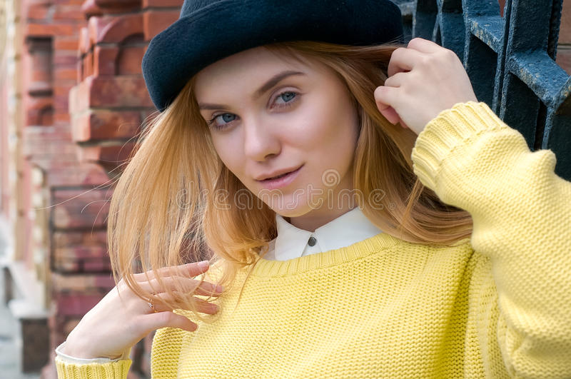 Girl in yellow sweater near red brick wall royalty free stock images