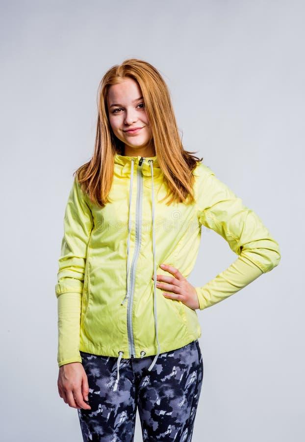 Girl in yellow sweatshirt and fitness leggings, studio shot stock photography