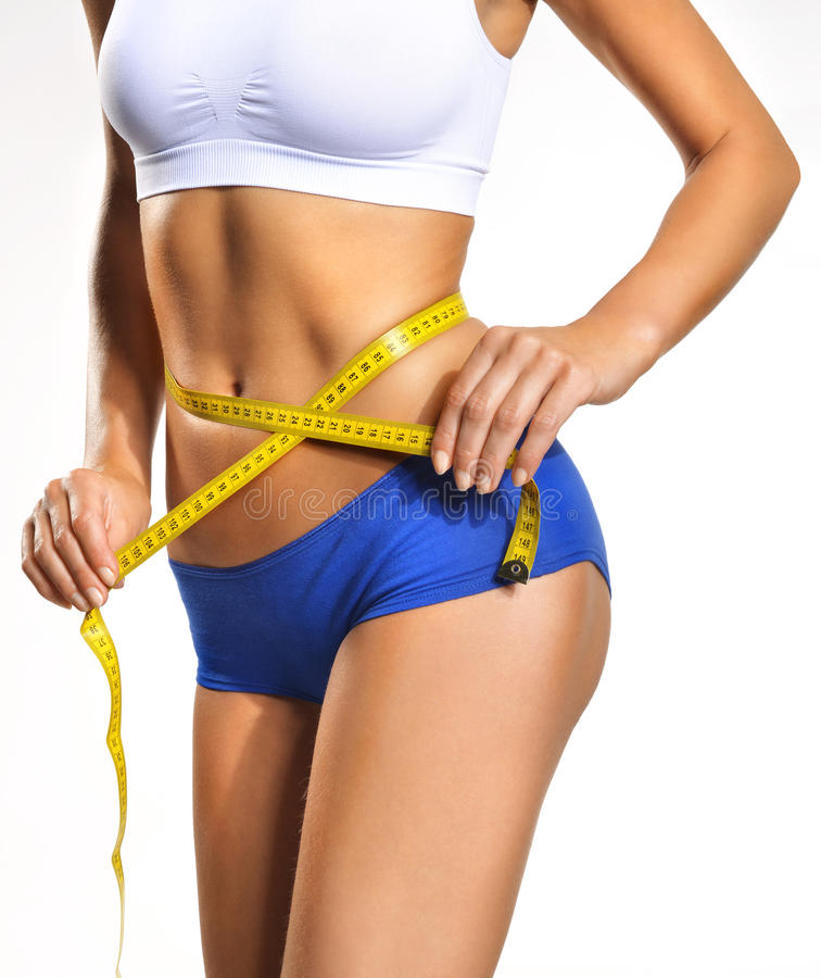 Girl with a yellow tape. Measure waist circumference stock photography