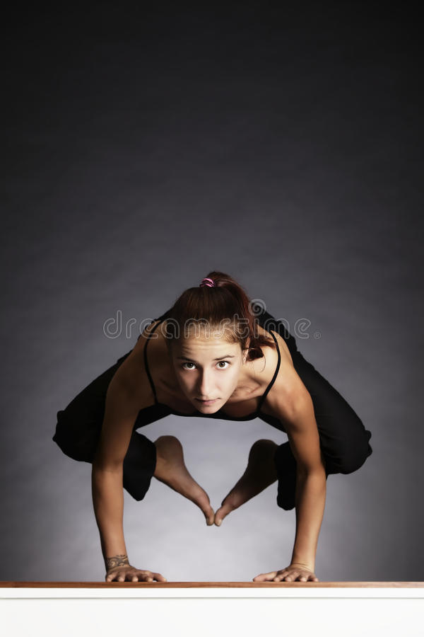 Girl in yoga crow pose.