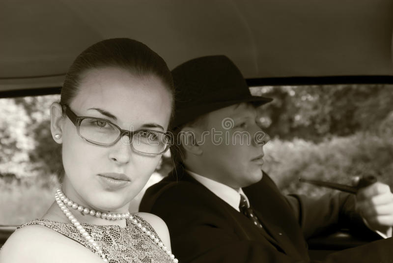 Girl and the young man in a car stock image