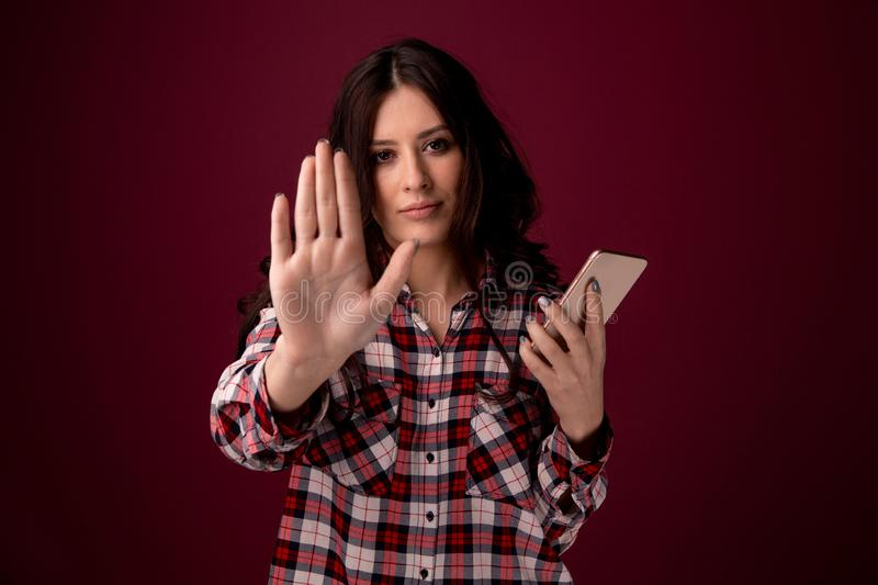 Girl or young woman holding mobile phone as internet stalked victim abused in cyberbullying or cyber bullying stress. Concept and in smartphone and network stock photo