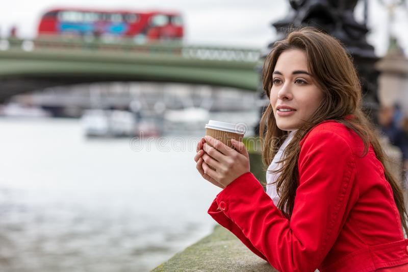 Woman Drinking Coffee by Westminster Bridge, London, England. Girl or young woman in a red coat drinking coffee in a disposable cup next to Westminster Bridge royalty free stock photography