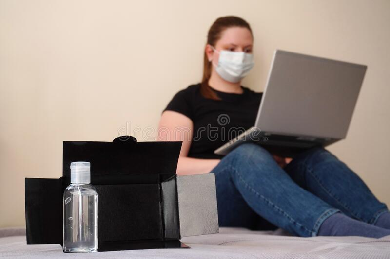 Girl or young woman works remotely at home in white medicine mask. hand antiseptic staying near the box during a coronavirus. Pandemic. use gel sanitizer in a royalty free stock photography