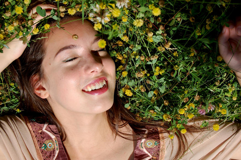 Girl/young womanlaying in the grass smiling. Portrait of a Girl/young woman laying in the green grass smiling, with sun shining on her face royalty free stock photos