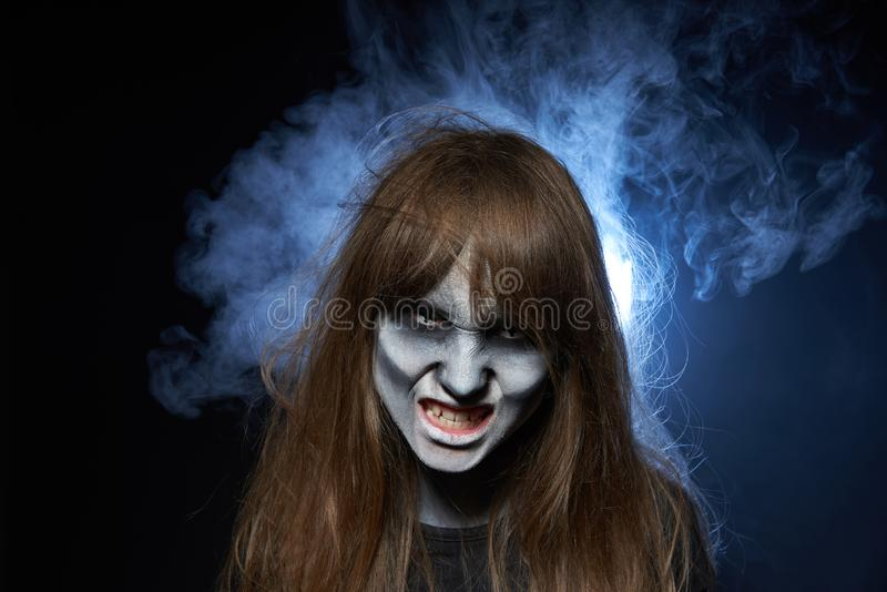 A girl with zombie makeup over dark background with smoke and backlight. Halloween zombie. Closeup portrait of a girl with zombie makeup showing her teeth over royalty free stock photo