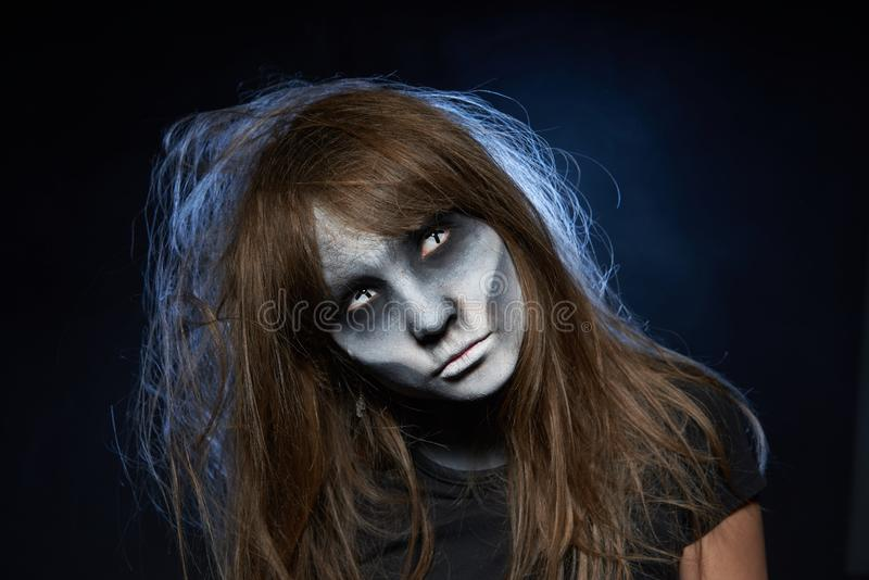 A girl with zombie makeup over dark background with smoke and backlight. Halloween zombie. Closeup portrait of a girl with zombie makeup looking at camera over royalty free stock photos