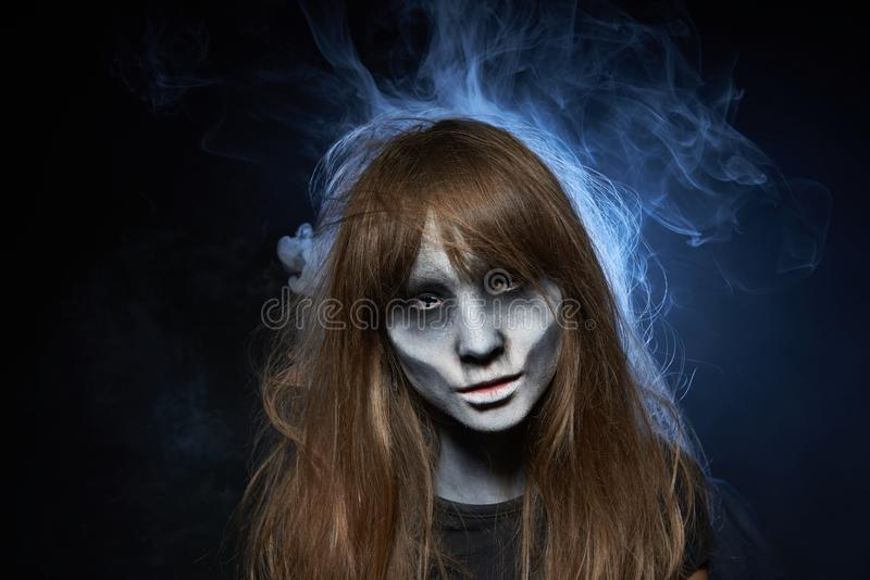 A girl with zombie makeup over dark background with smoke and backlight. Halloween zombie. Closeup portrait of a girl with zombie makeup looking at camera over stock photos