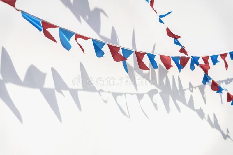 Girland av mångfärgade flaggor av triangulär form på ljus bakgrund med skugga, reflexion Modern bakgrund, baner royaltyfri fotografi