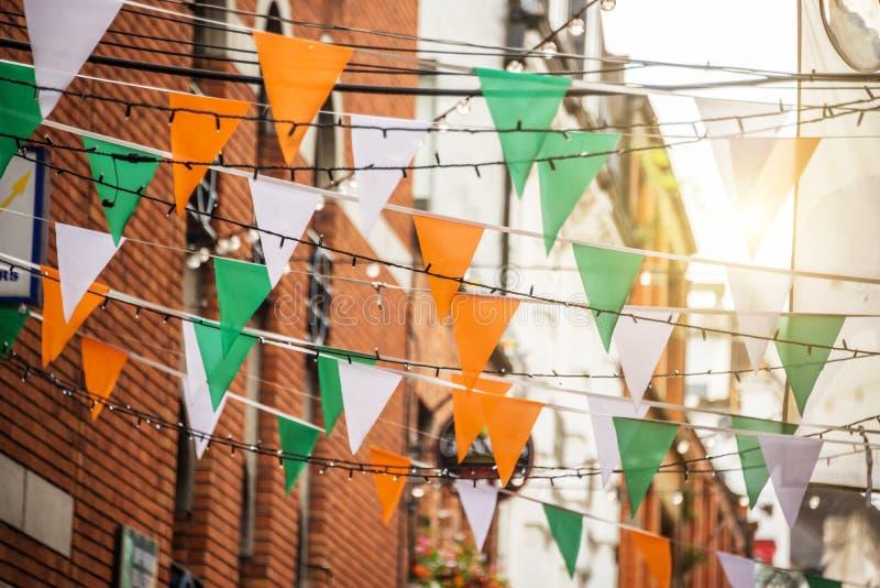 Girlanden med den irländska flaggan färgar i en gata av begreppet för Dublin, Irland - St Patrick dagberöm arkivbilder