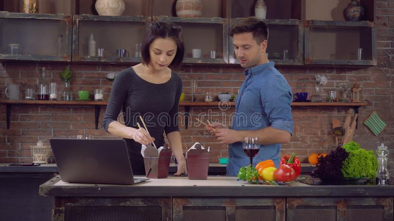 Girlfriend and boyfriend enjoy date at home. Family relish chinese food in kitchen. Happy couple in love eating diner from takeout restaurant. Young smiling royalty free stock image