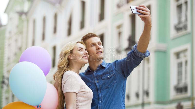 Girlfriend and boyfriend hugging in street and taking selfie, romantic photos royalty free stock images