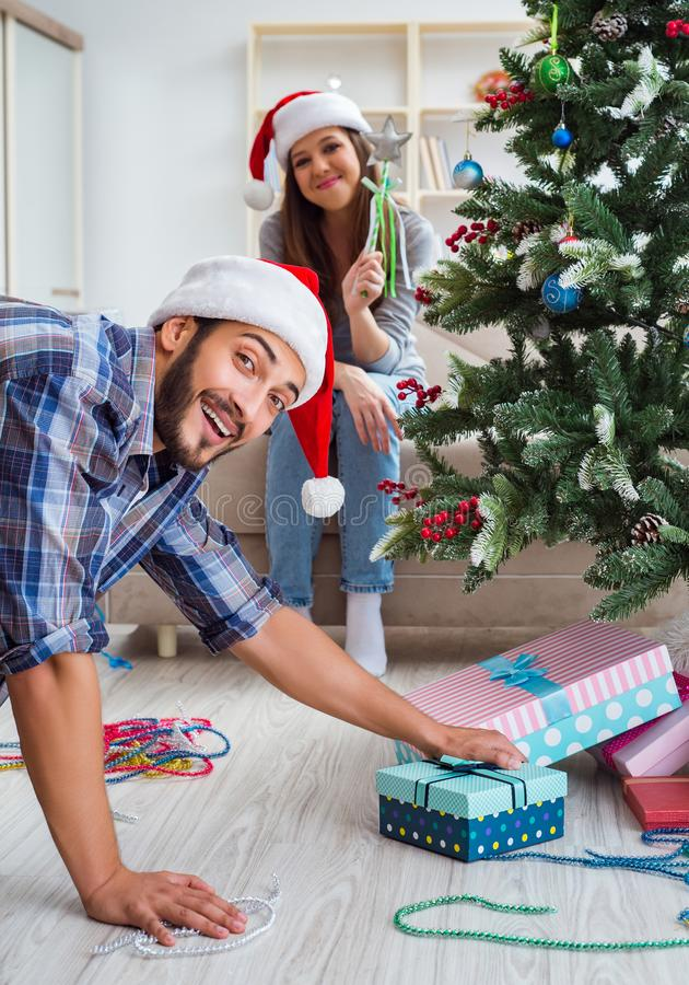 Girlfriend and boyfriend opening christmas gifts. The girlfriend and boyfriend opening christmas gifts royalty free stock photography