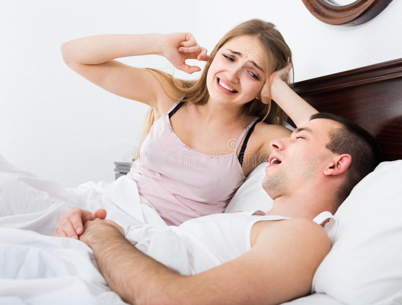 Girlfriend cannot stand guy snoring loudly in sleep. Upset american girlfriend cannot stand guy snoring loudly in sleep stock image